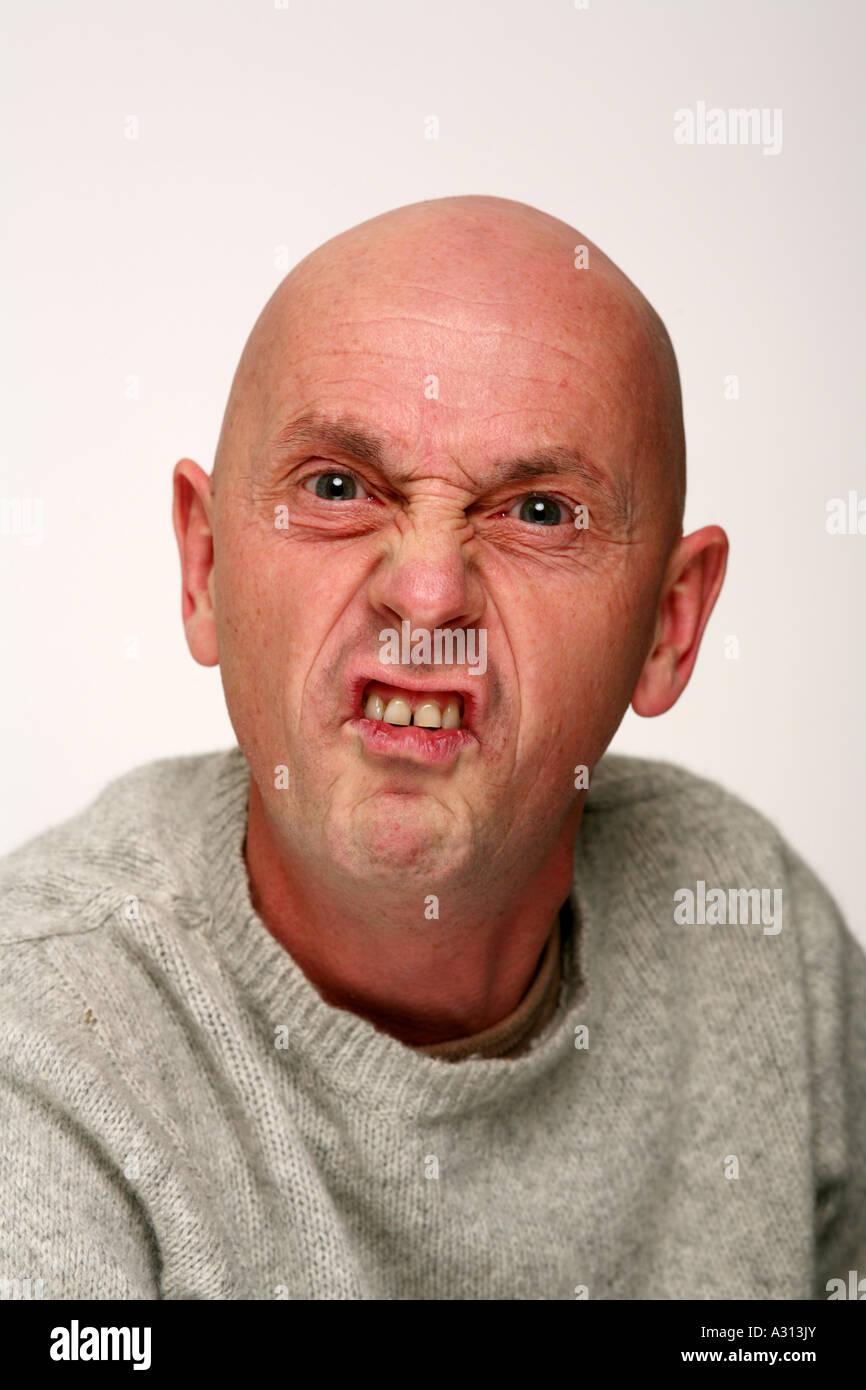 Bald man being belligerent to camera - Stock Image
