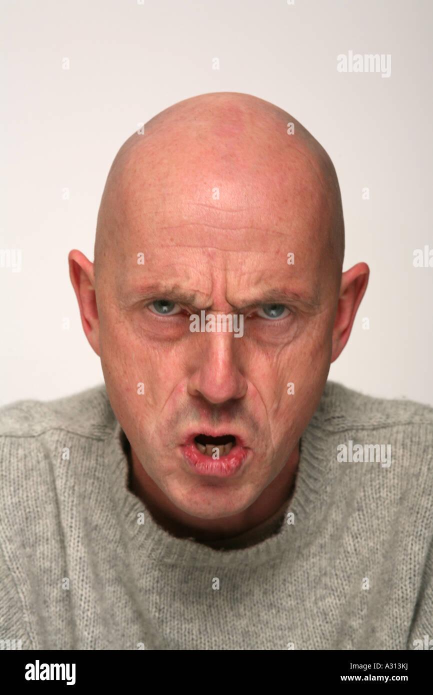 Bald man making aggressive face to camera - Stock Image