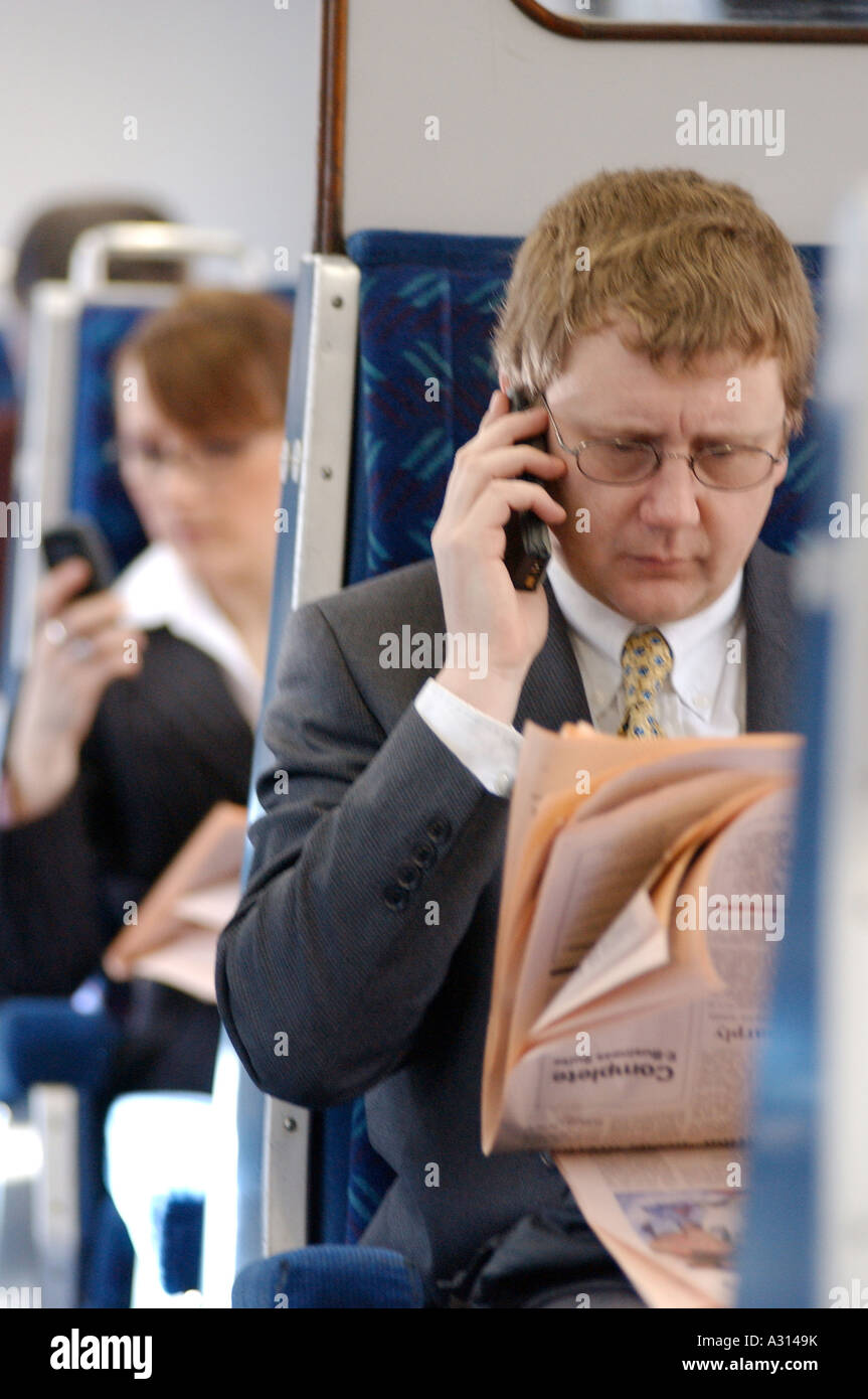 Royalty free photograph of British business man with FT and mobile phone commuting on train London UK - Stock Image