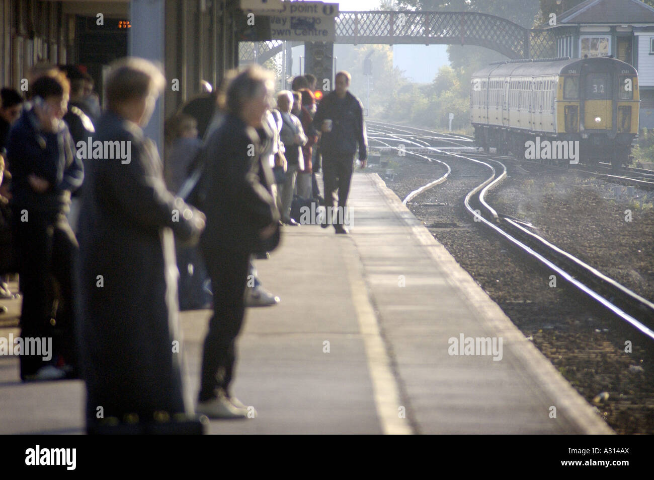 commuters train platform people daily journey work - Stock Image
