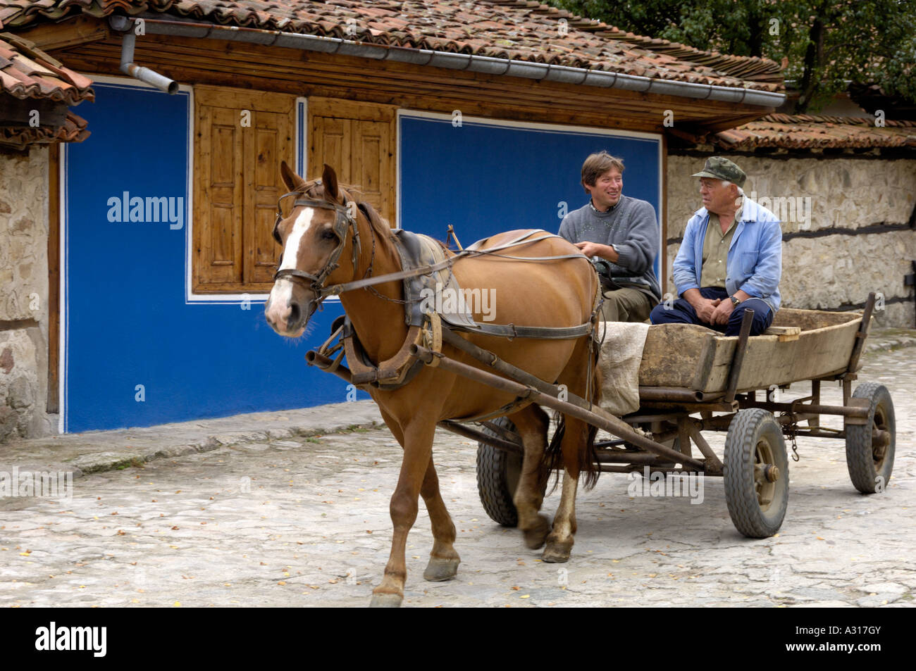 People riding horsecart Koprivshtitsa town museum Bulgaria East EuropeStock Photo