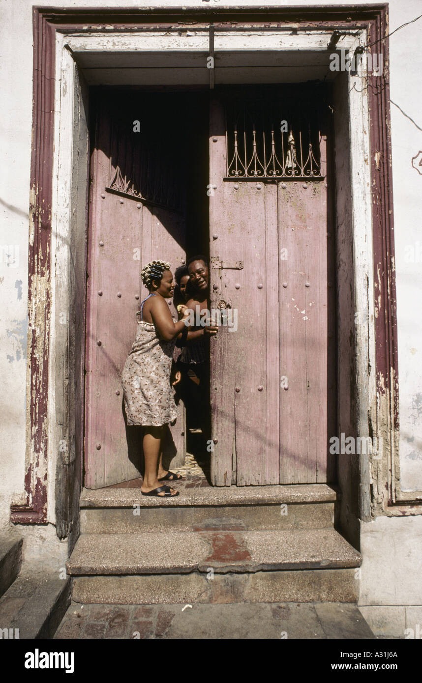 A group of people laughing in a doorway in 'Old Town', Havana, Cuba. One of the women has her hair in rollers - Stock Image