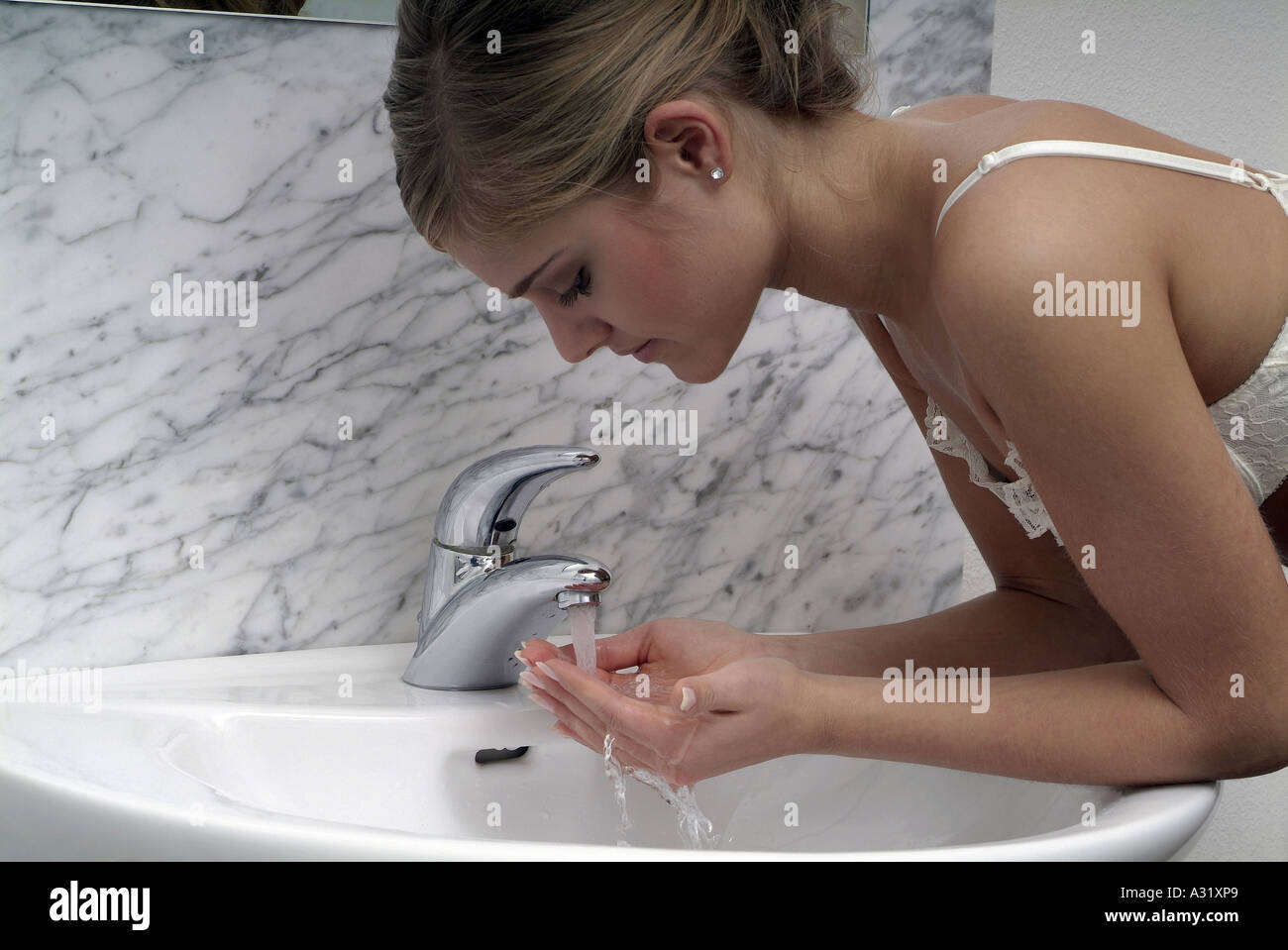 Young woman with hands cupped under running tap - Stock Image