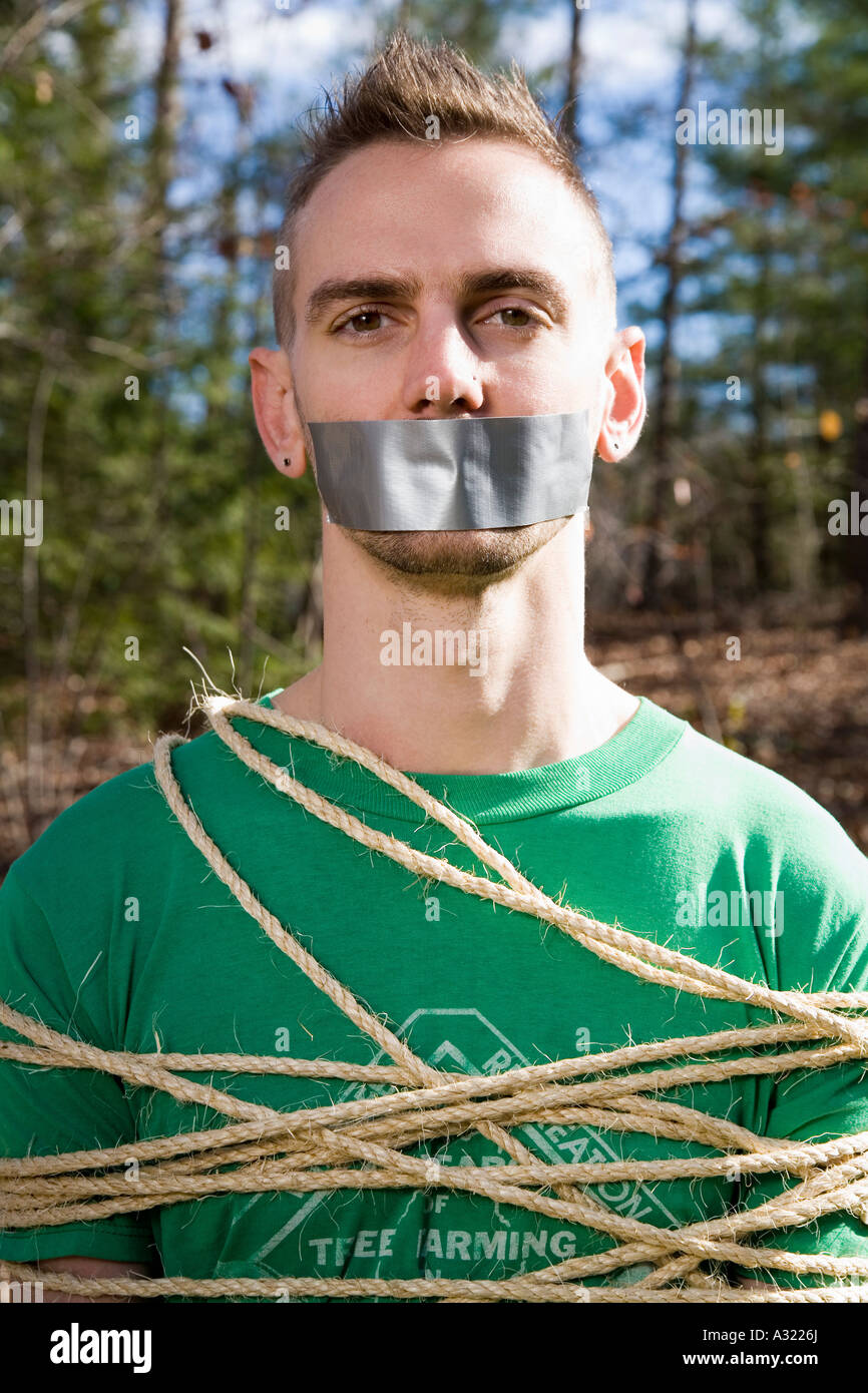 Man standing in the woods bound in rope and with adhesive tape covering his mouth - Stock Image