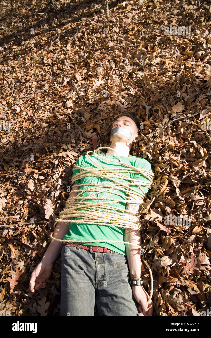 Man lying on the ground bound in rope and with adhesive tape covering his mouth - Stock Image