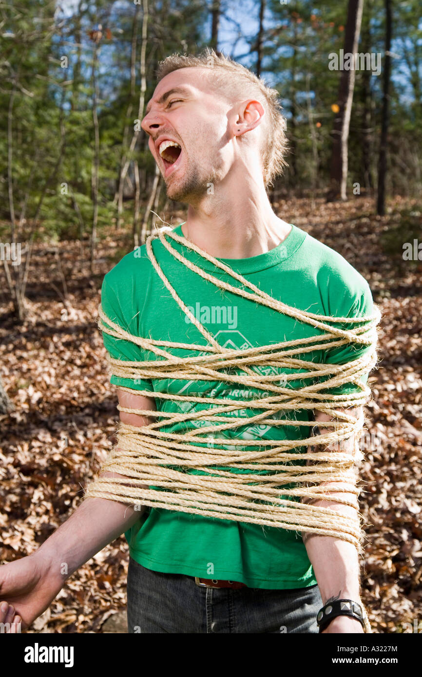 Man bound in rope and shouting in the woods - Stock Image