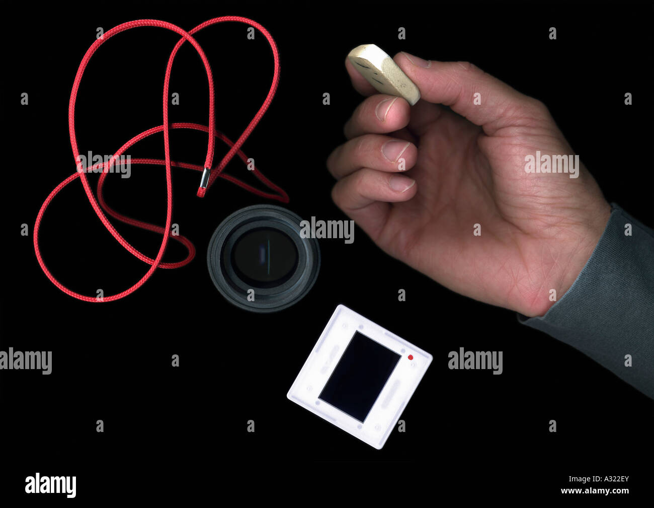 Man holding an eraser next to photographic equipment - Stock Image