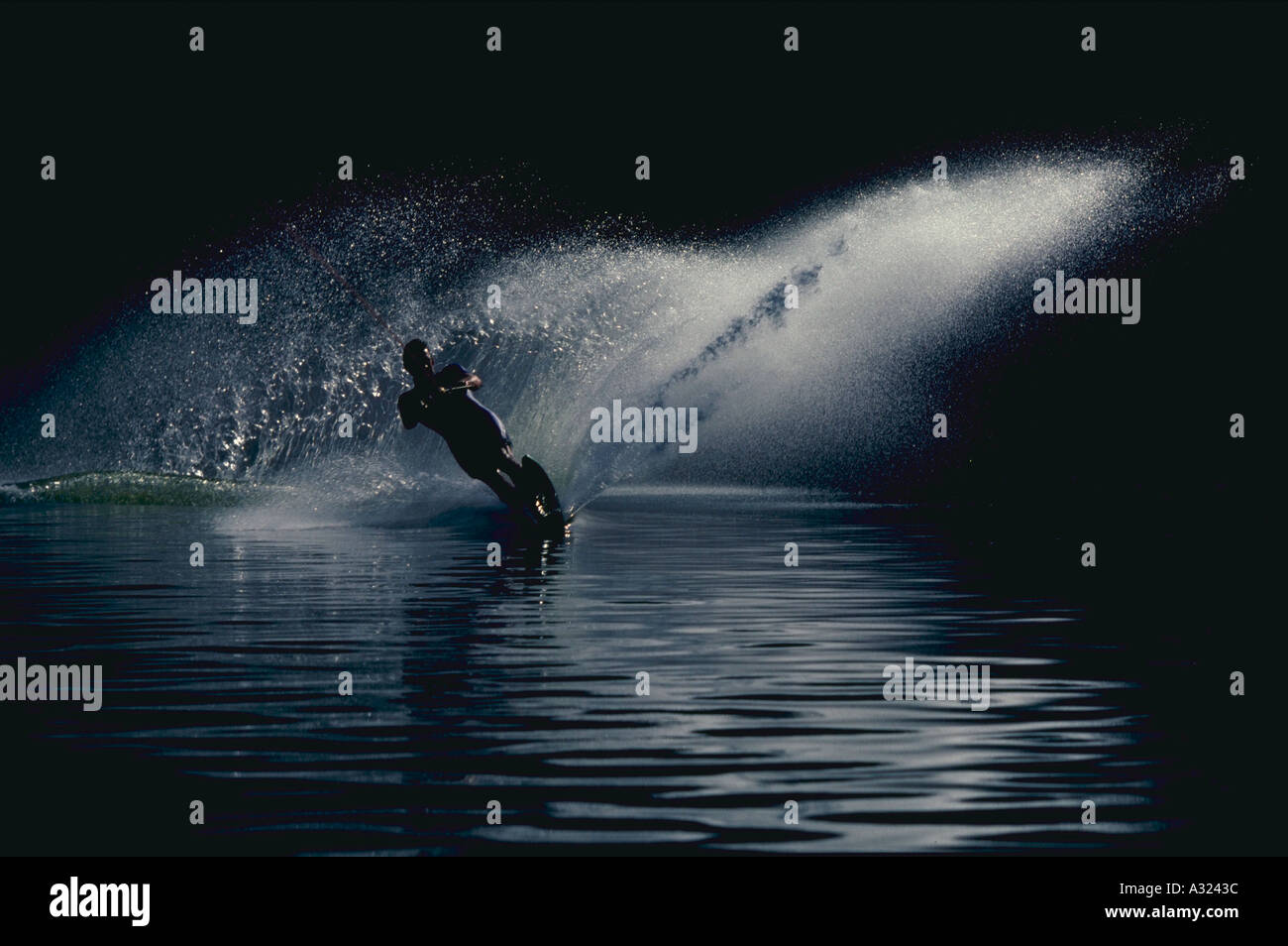 Man water skiing in morning light with spray of water - Stock Image