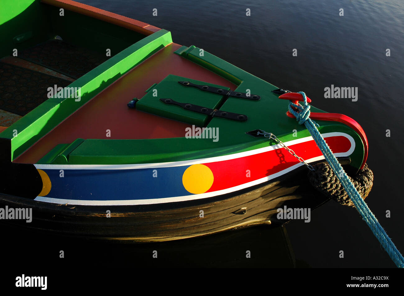Josher style bow of a British narrowboat painted in the classic colours of green red blue and yellow - Stock Image