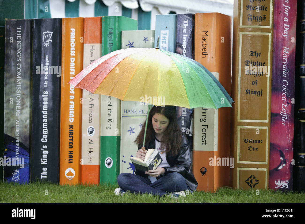 A visitor to the Hay on Wye book festival in Powys, Wales, reading in front of a display of oversize books in the - Stock Image