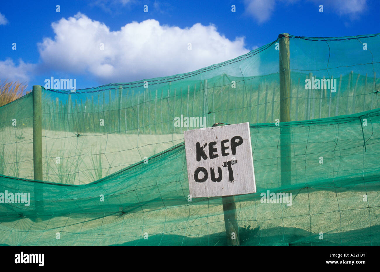 Rough handpainted sign stating Keep out in front of green nylon netting and wire and sheep fencing on sand dunes Stock Photo