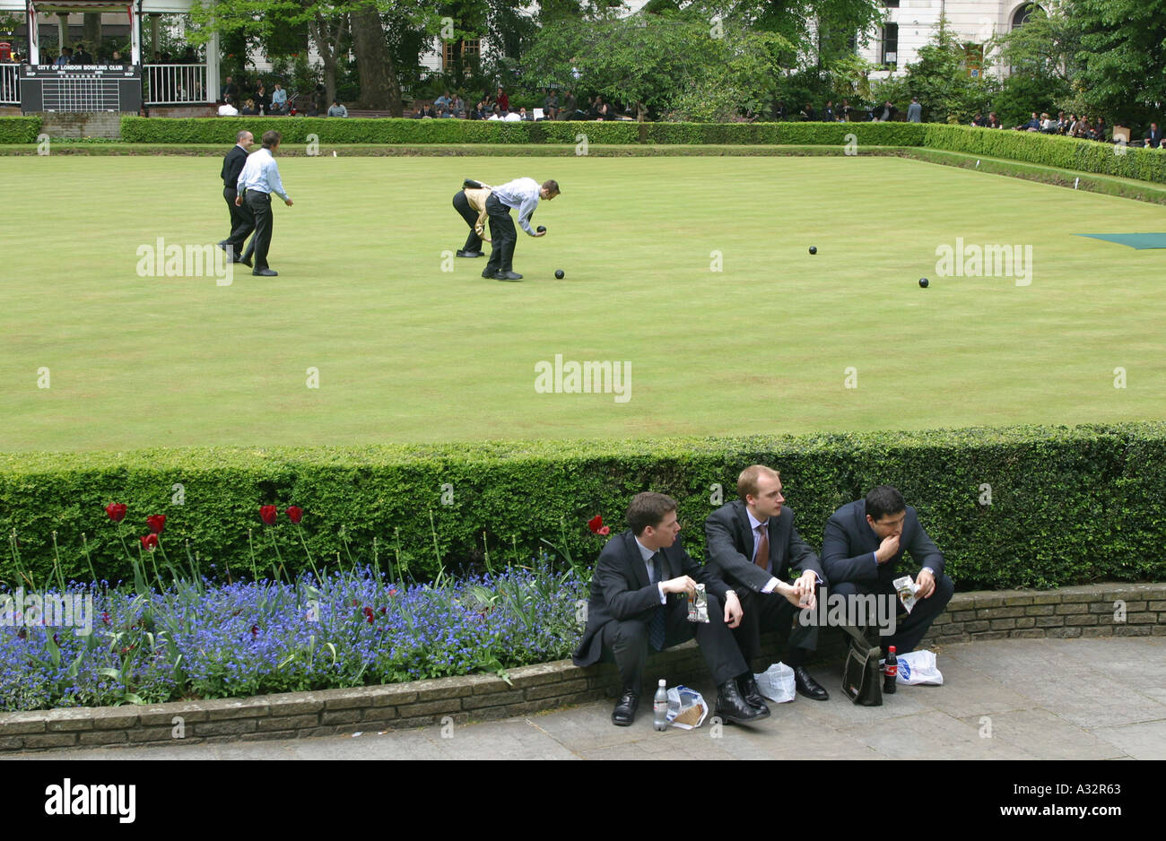 people play bowls on the grass whilst three men eat lunch beside the hedge at finsbury circus - Stock Image