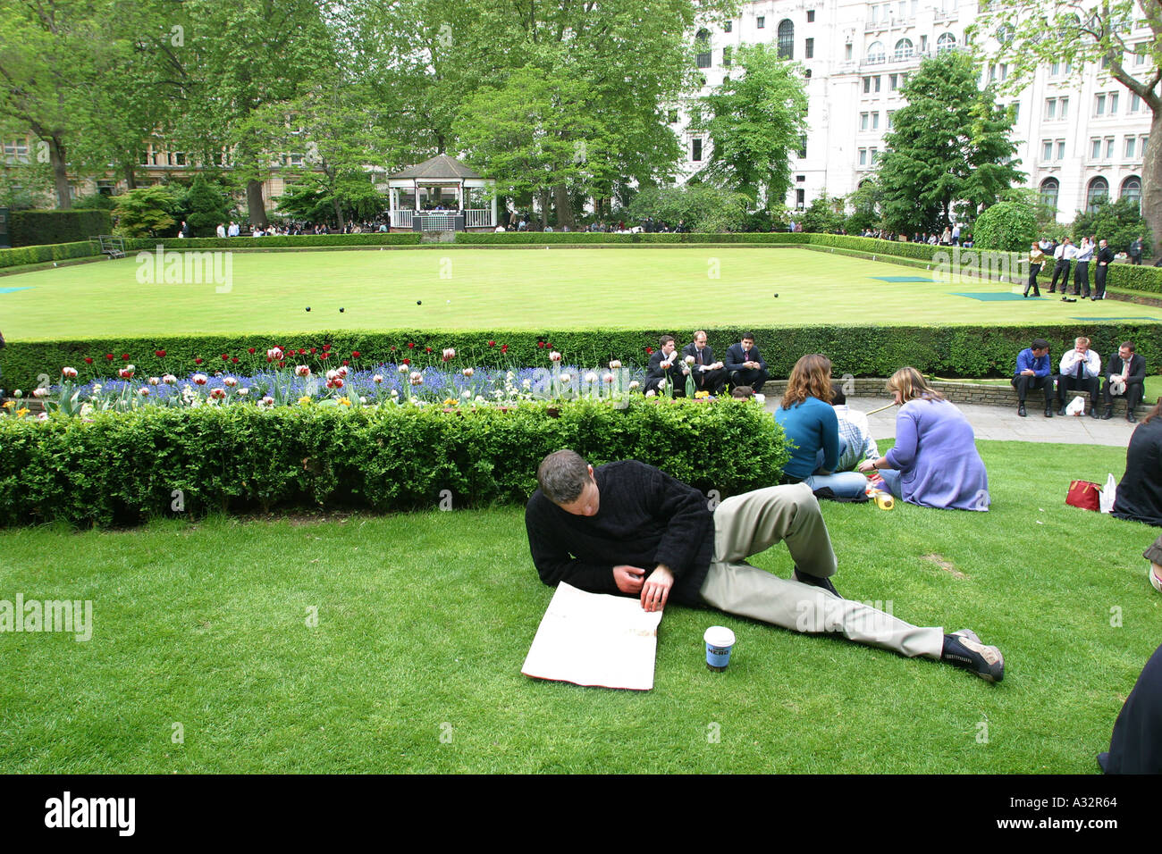 a man lying and reading on the grass at finsbury circus - Stock Image