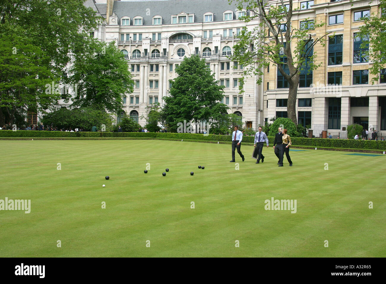 people play bowls on the grass surrounded by offices at finsbury circus - Stock Image