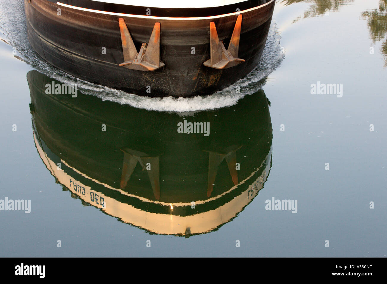 Bow of a ship and its reflexion on the water surface - Stock Image