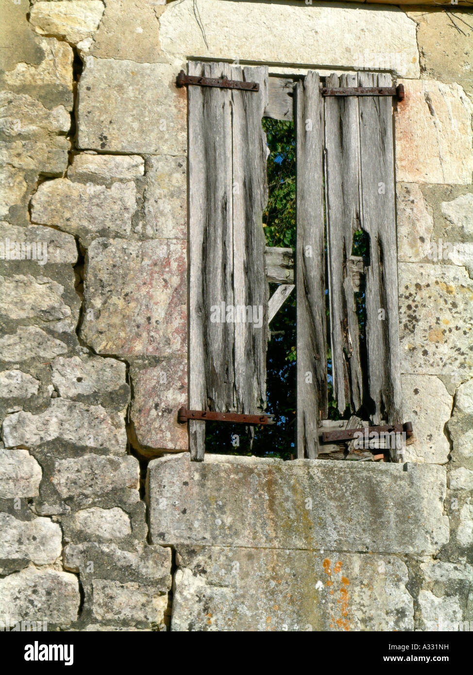 remains of a house broken wall with a window and broken down cutters - Stock Image