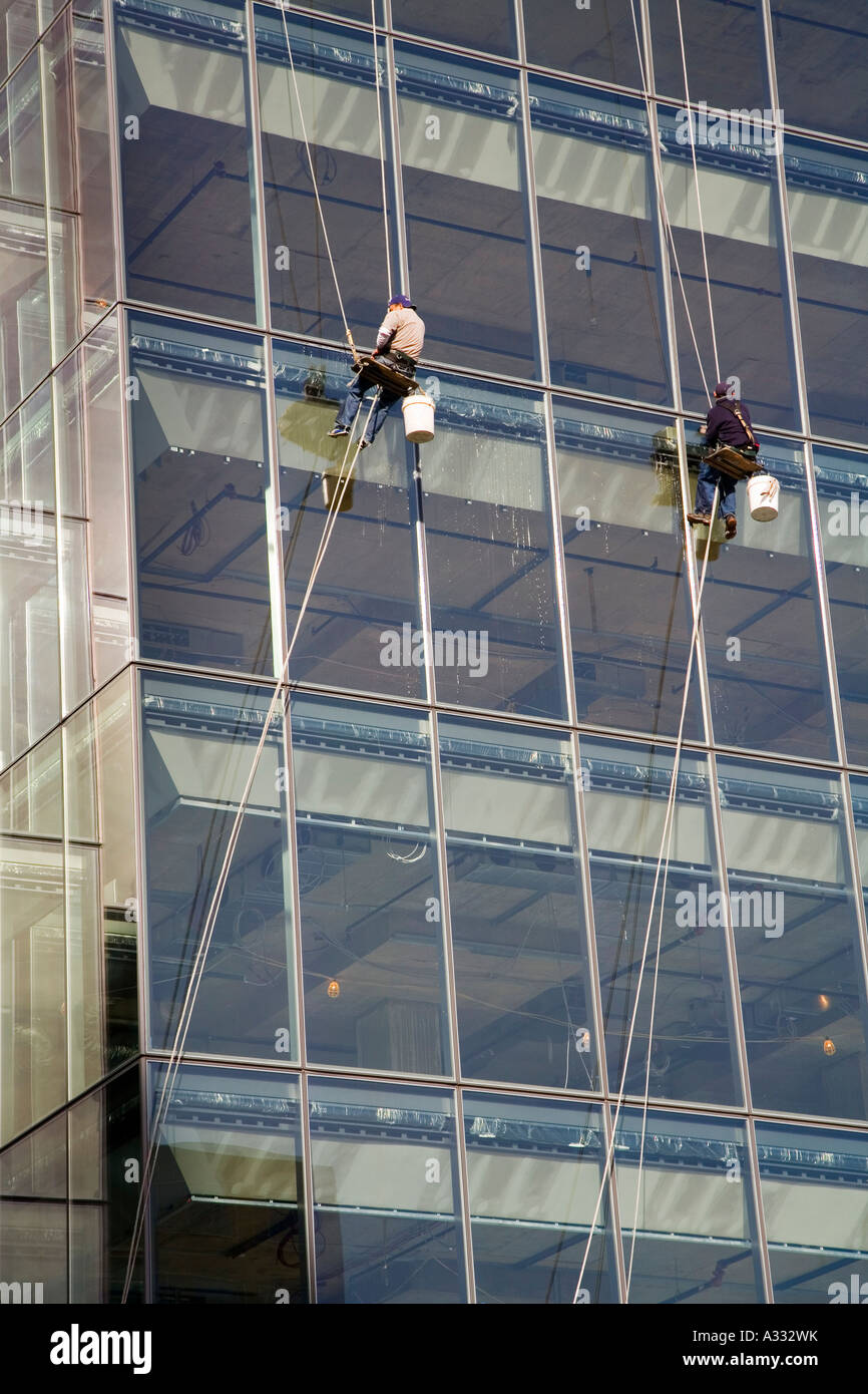 Washington DC Two workers wash windows as they hang from ropes high up on an office building - Stock Image
