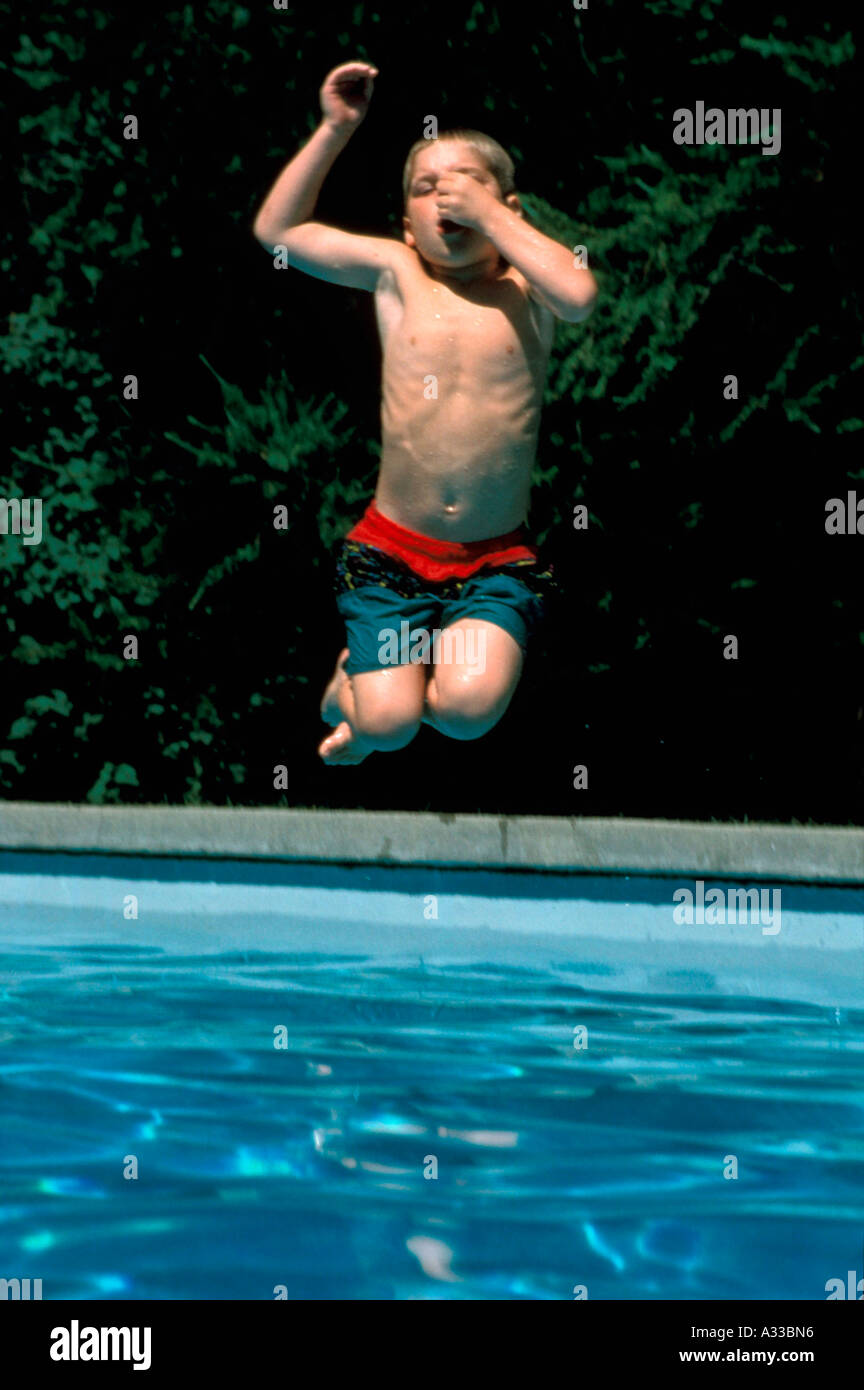 Boy jumps in pool M F64 - Stock Image