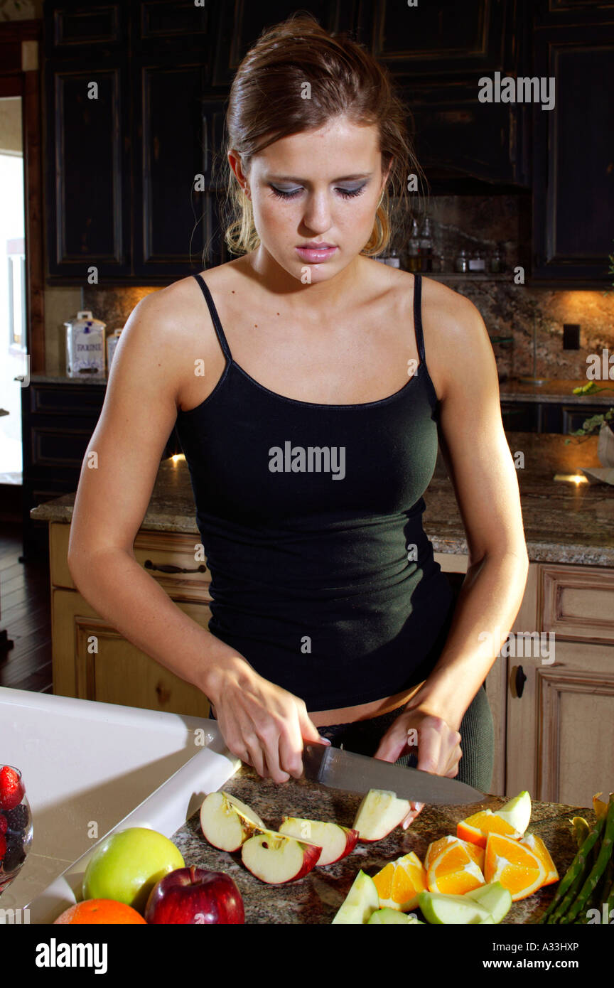 Young woman preparing healthy meal of fruits and vegetables in the kitchen. - Stock Image