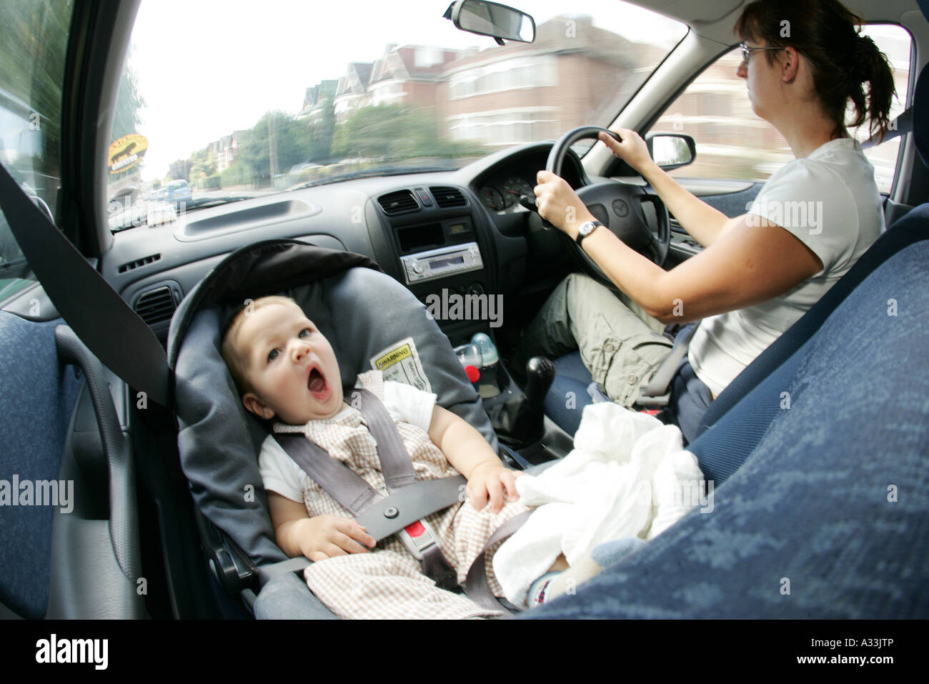 mother and baby driving in car with baby in front seat baby carrier