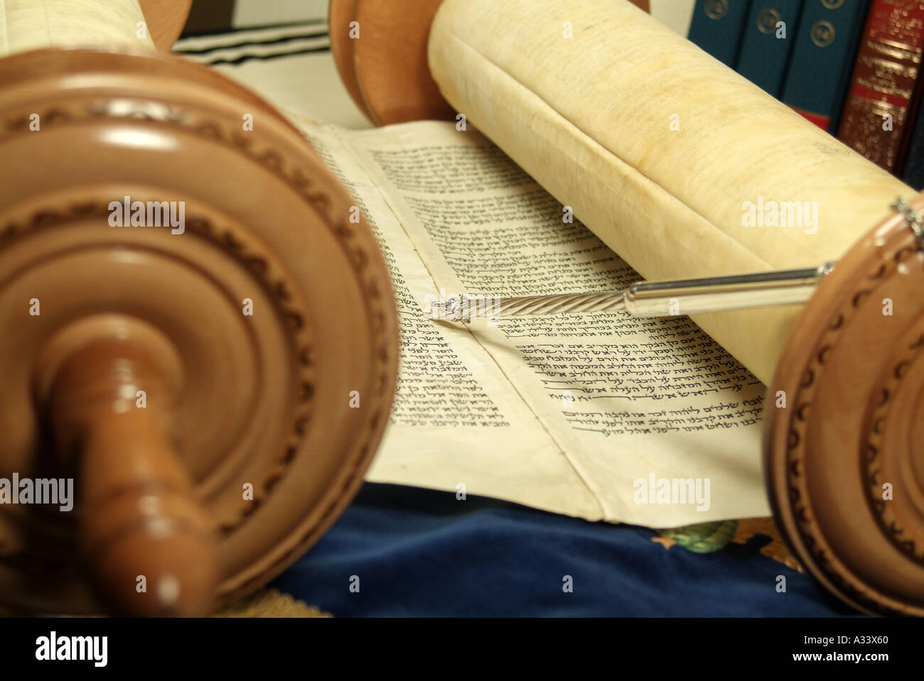 Open Torah scroll with silver yad pointing to Hebrew word. Holy Jewish books in background - Stock Image