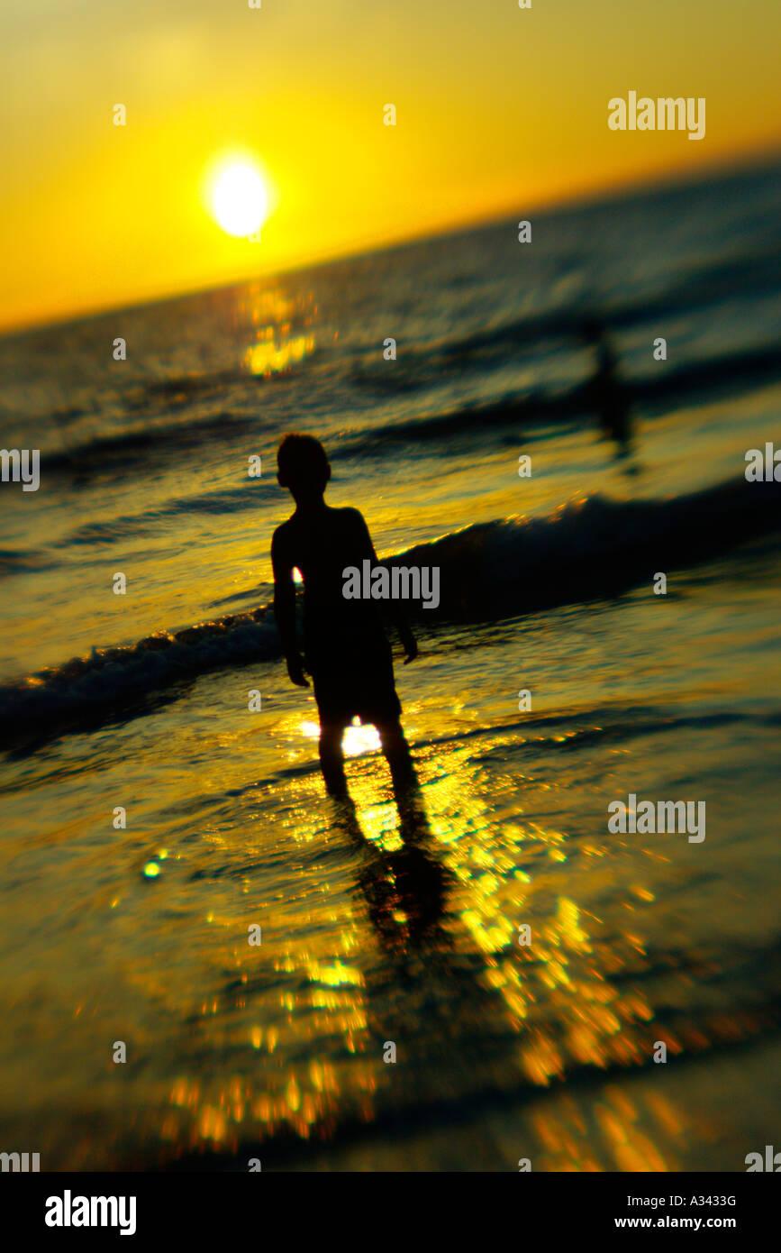A boy watches the sunset from Ke'e Beach, Kauai, Hawaii - Stock Image