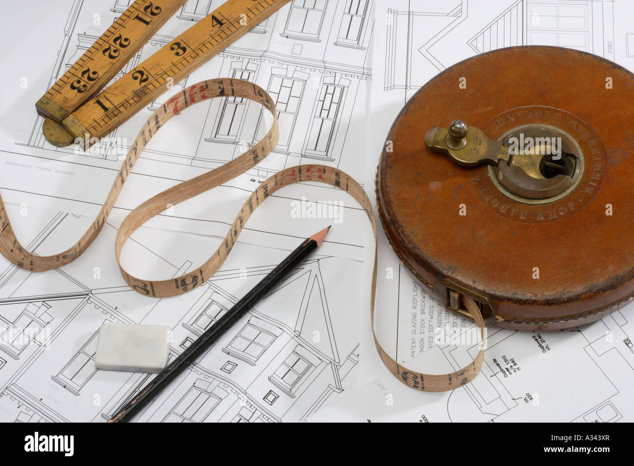 Tape measure and pencil on Architects technical drawings - Stock Image