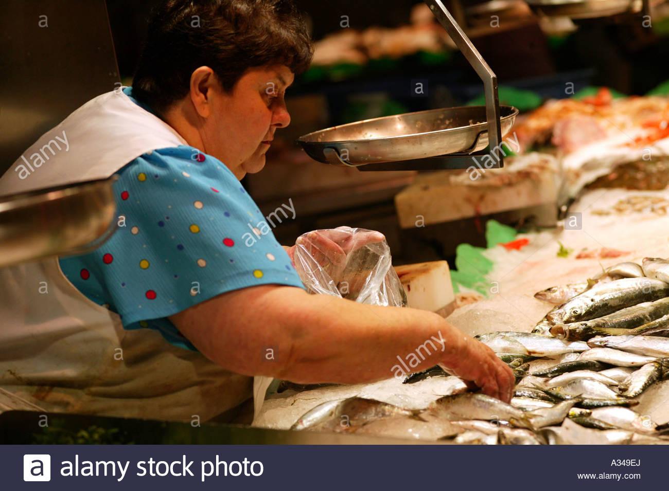 Woman working at a fish stall at Barcelona's famous indoor food market La Boqueria off La Rambla central Barcelona - Stock Image