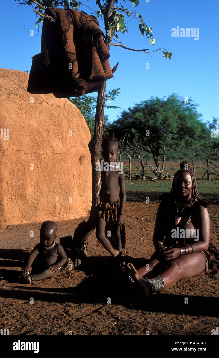 Himba or Ovahimba trib woman sitting in front of her hut inside Kraal with children aokoveld Namibia Africa - Stock Image