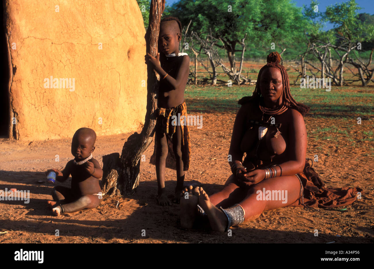 Himba Ovahimba tribe woman with children sitting in front of hut inside Kraal Kaokoveld Namibia Africa - Stock Image