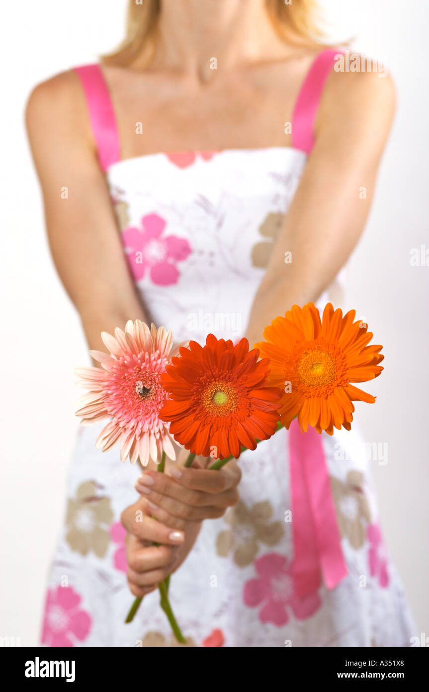 Woman in a summer sundress holding a bouquet of 3 Gerbera daisies - Stock Image