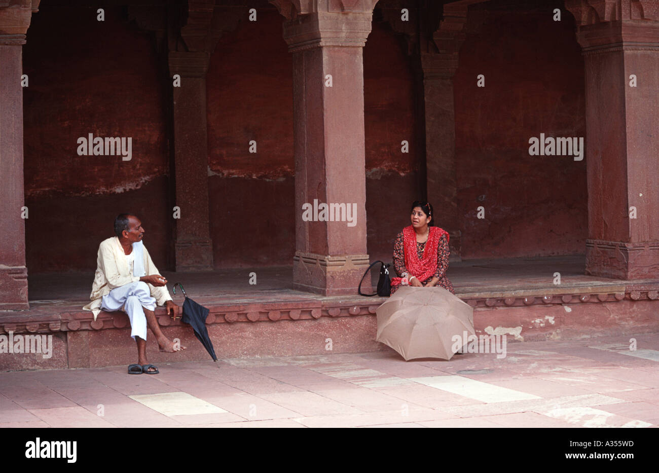 An Indian man and woman sitting chatting at Fatephur Sikri India - Stock Image