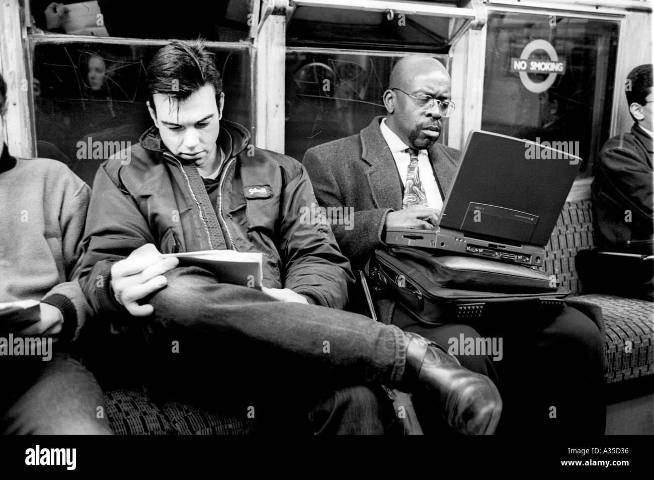 Man doing his Homework on the tube London England Britain UK - Stock Image