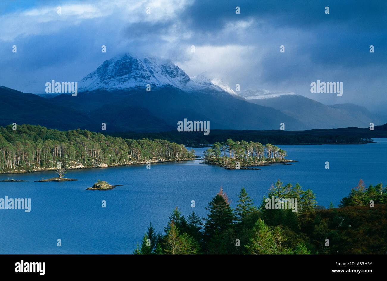 a snow capped Slioch rising above Loch Maree Wester Ross Scotland UK - Stock Image