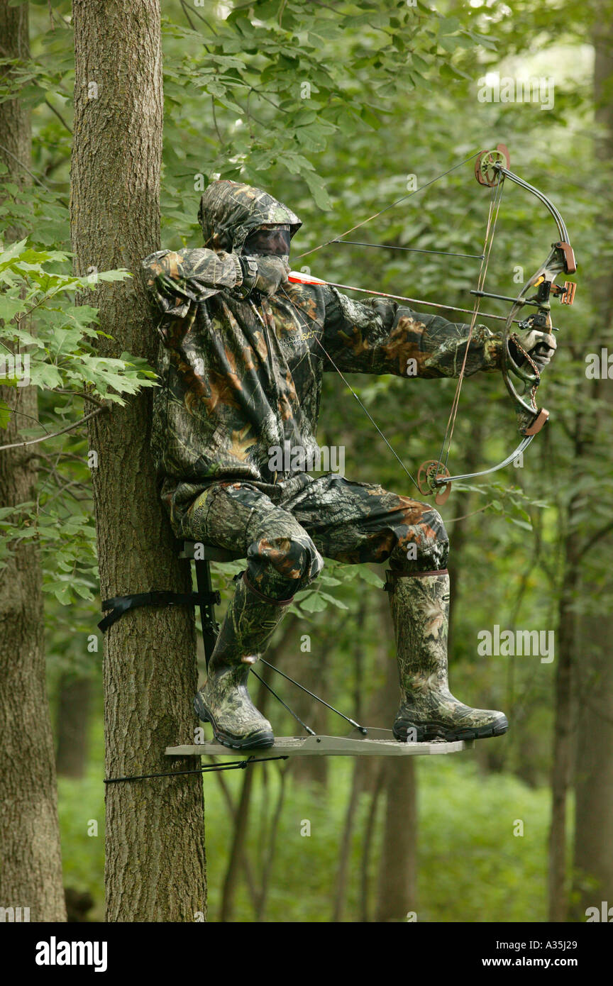 bow hunter in camouflage gear on a tree stand with bow and. Black Bedroom Furniture Sets. Home Design Ideas