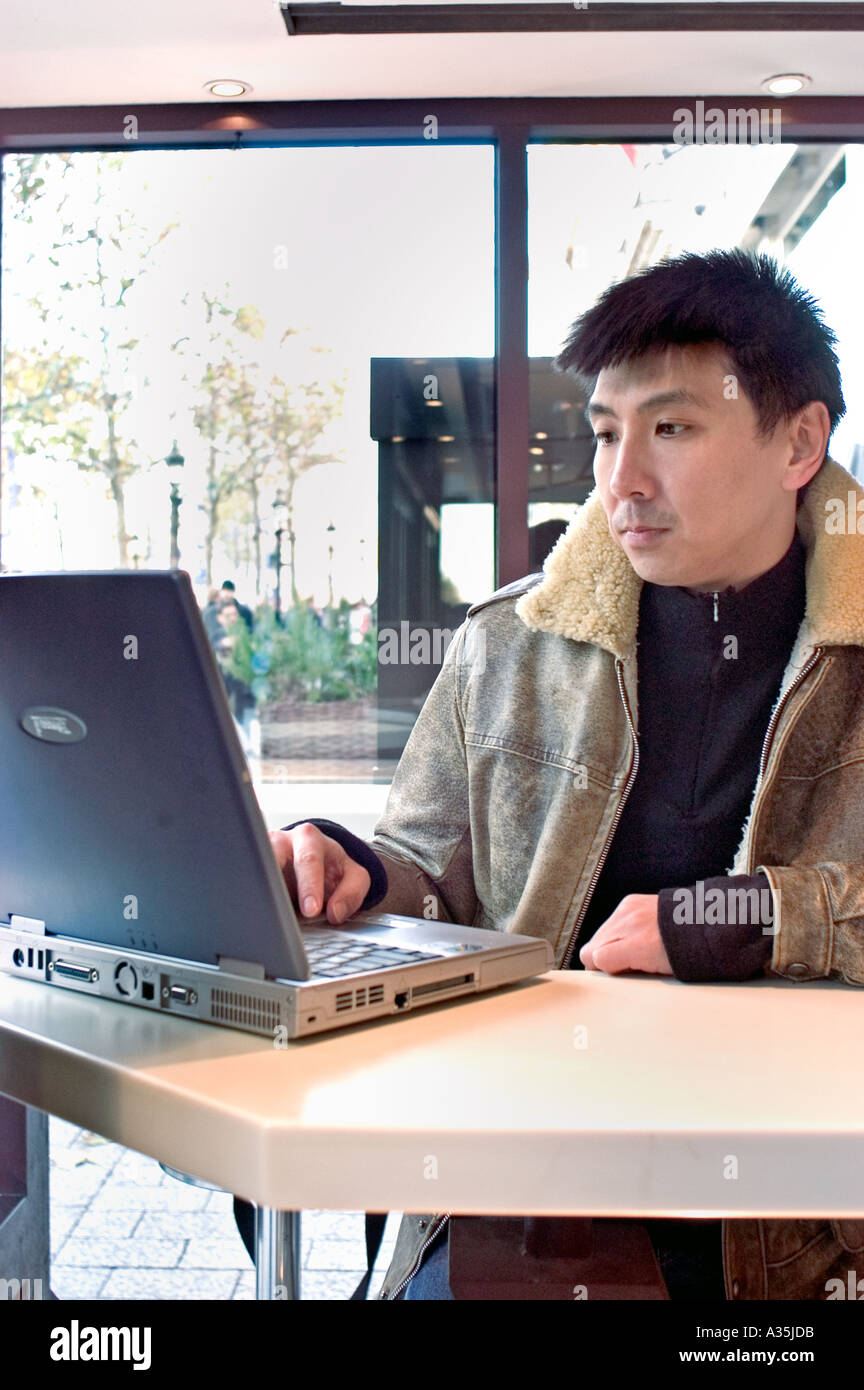 Chinese Man in Mc-Donald Restaurant, Looking at  Laptop Computer Screen on Table - Stock Image