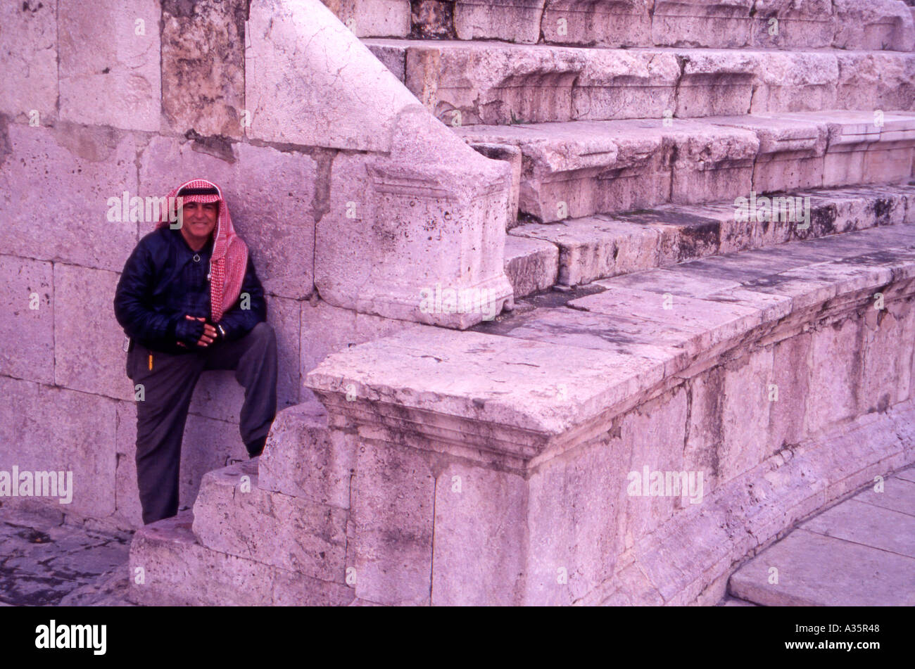 Steve an official Tour Guide at the Roman Amphitheatre in Amman Jordan wearing the traditional Jordanian Keffiyeh head cloth - Stock Image