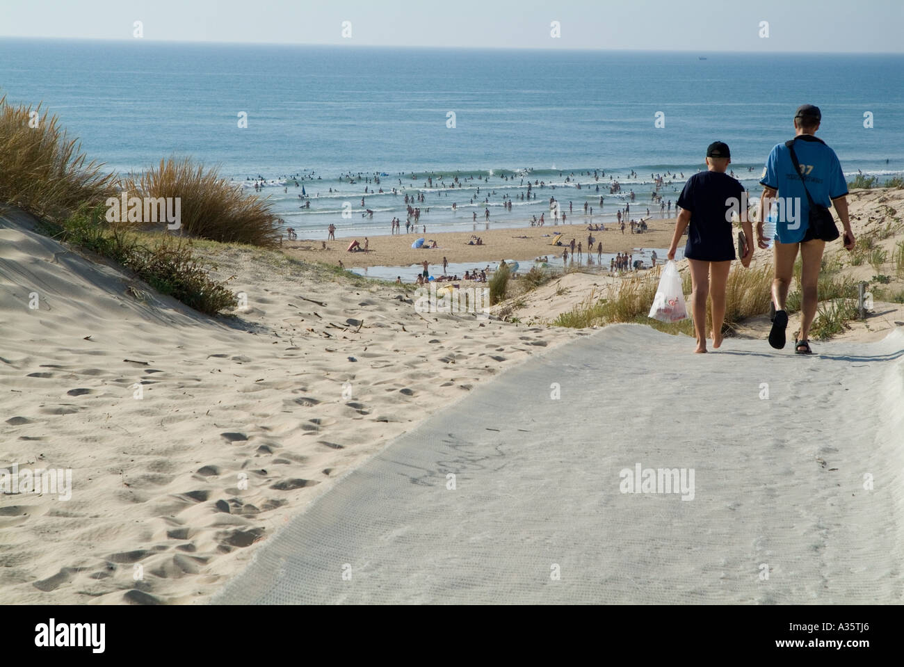 Father and son walking down to the beach Le Porge plage on the Atlantic Ocean, Aquitaine, France - Stock Image