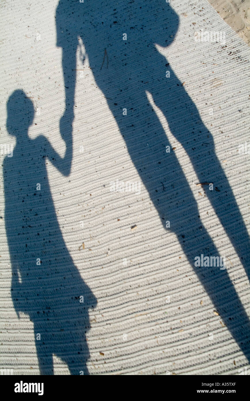 Shadow Of A Father And His Daughter Holding Hands Walking On A Mat