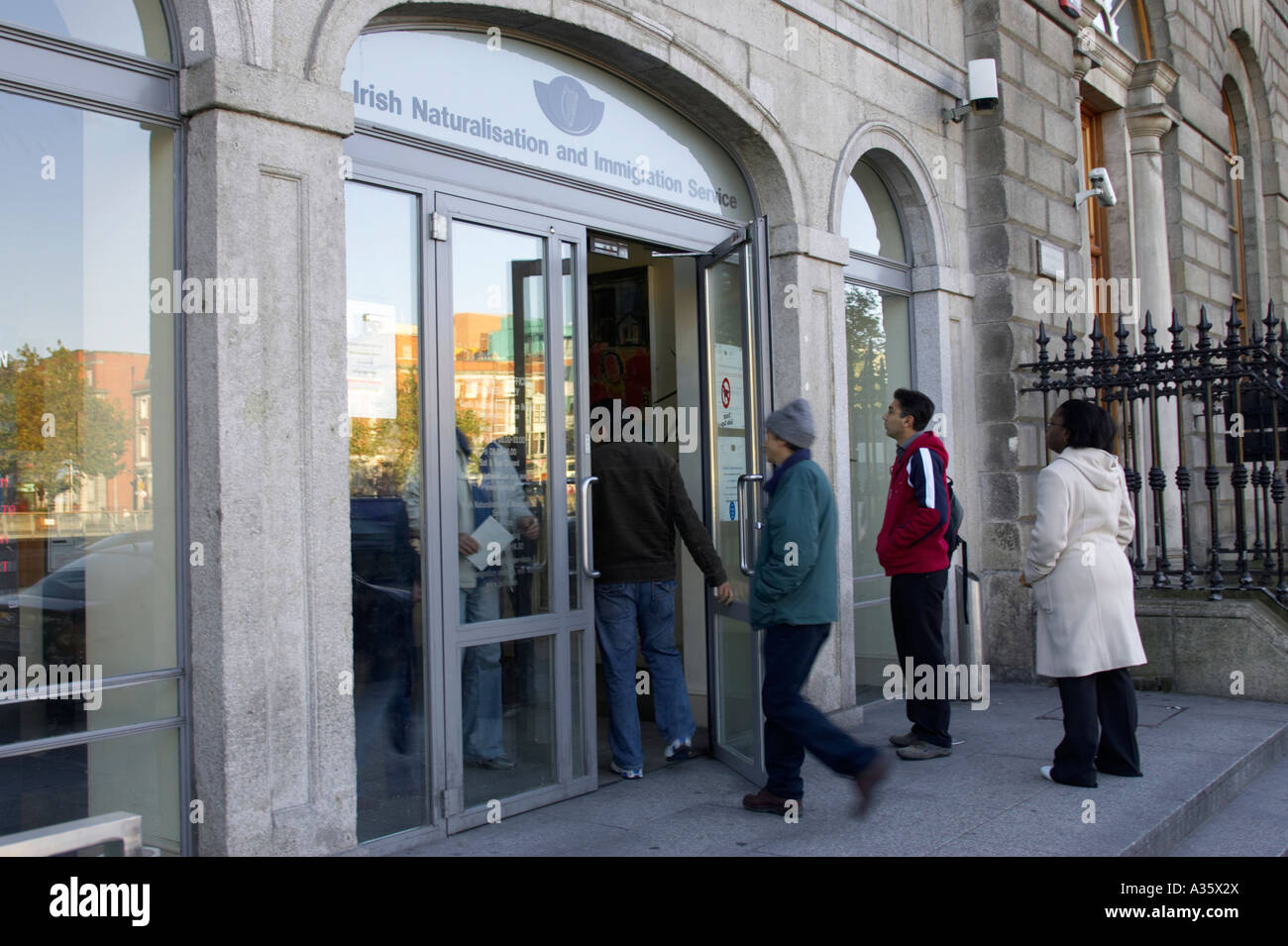 black and asian immigrants enter the Irish Naturalisation and Immigration Service in Dublin - Stock Image