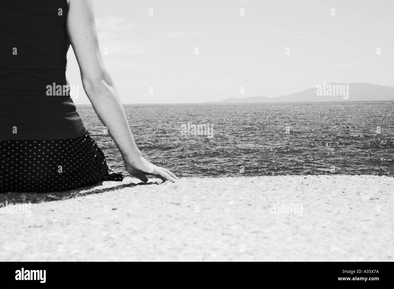 Woman Sitting At Sea - Stock Image