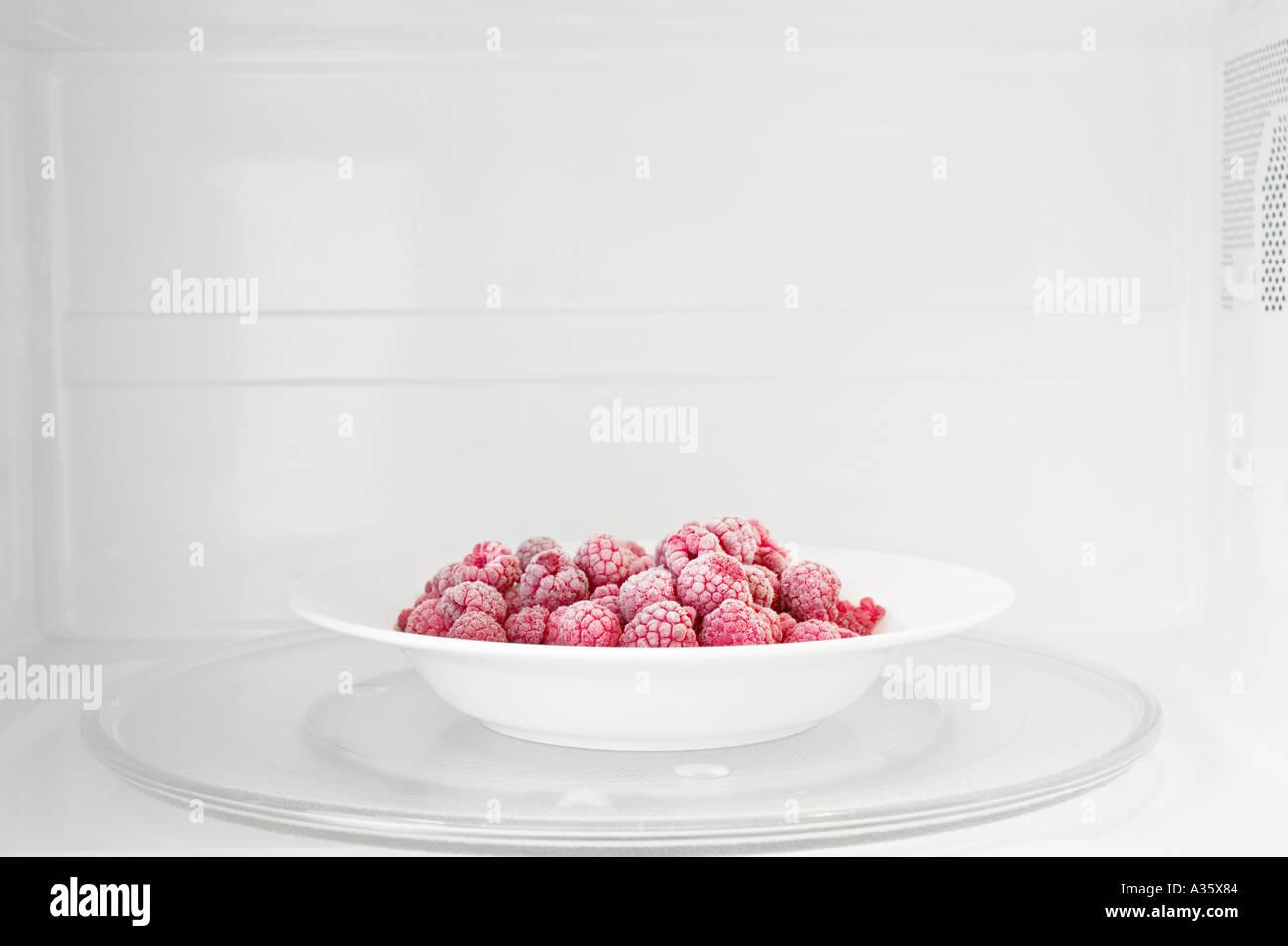 Plate Of Frozen Raspberries In Microwave Oven - Stock Image