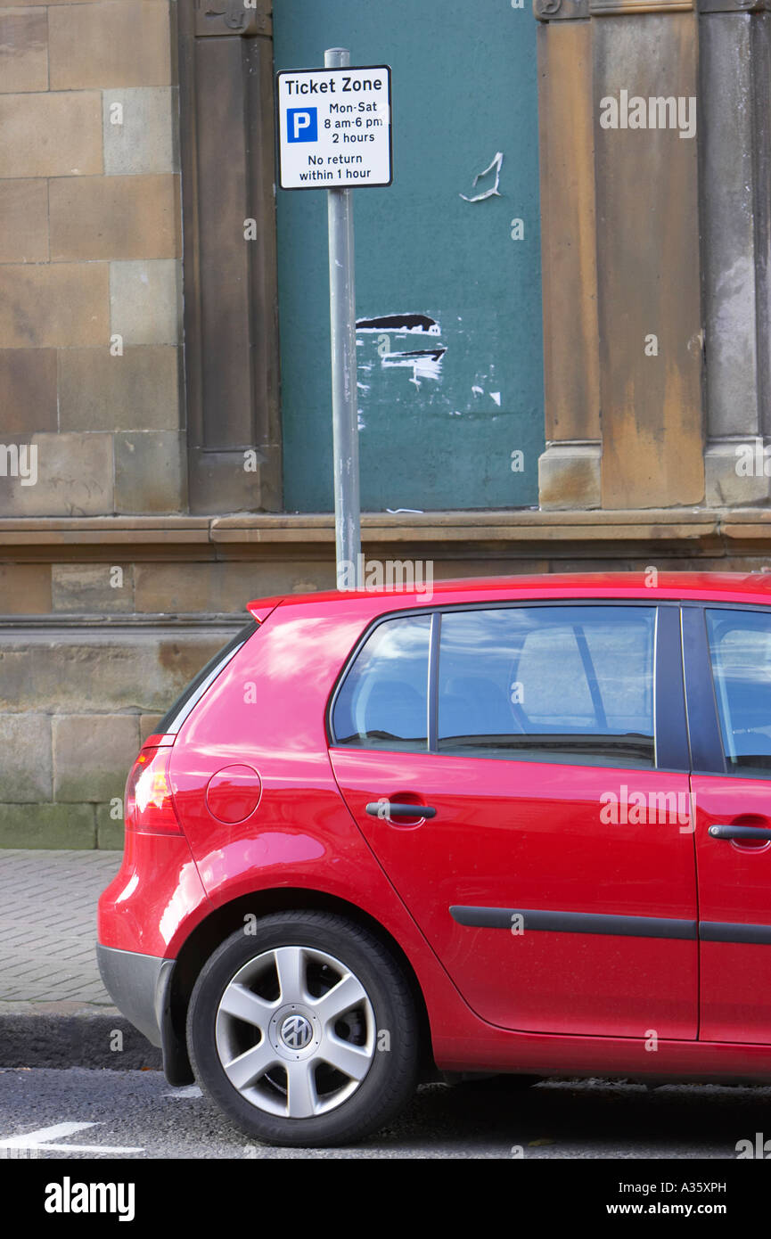 read of red volkswagen golf vw car parked in designated street parking spot on road beside ticket zone sign - Stock Image