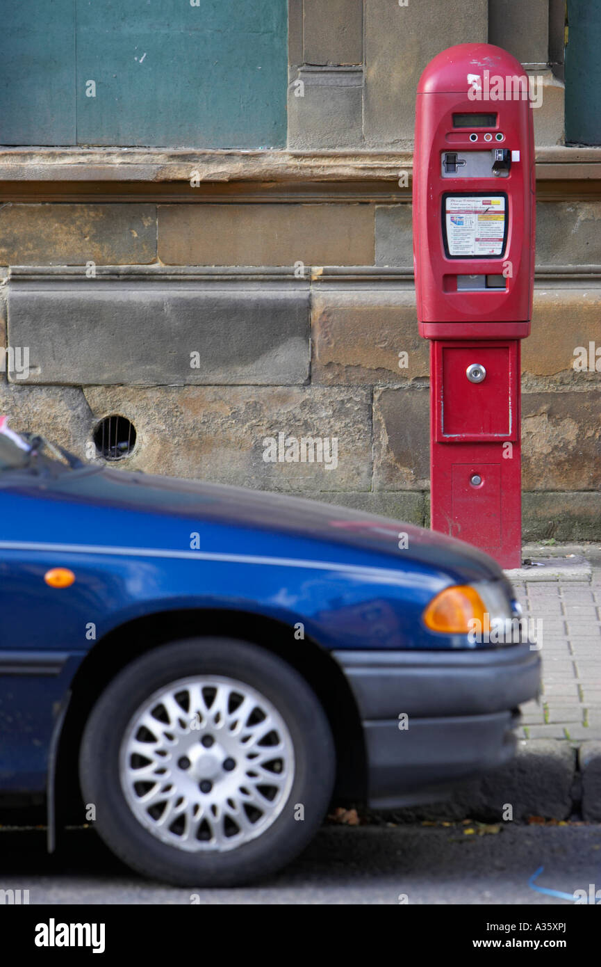 front of blue car parked in designated street parking spot on road in front of red electronic car parking ticket - Stock Image