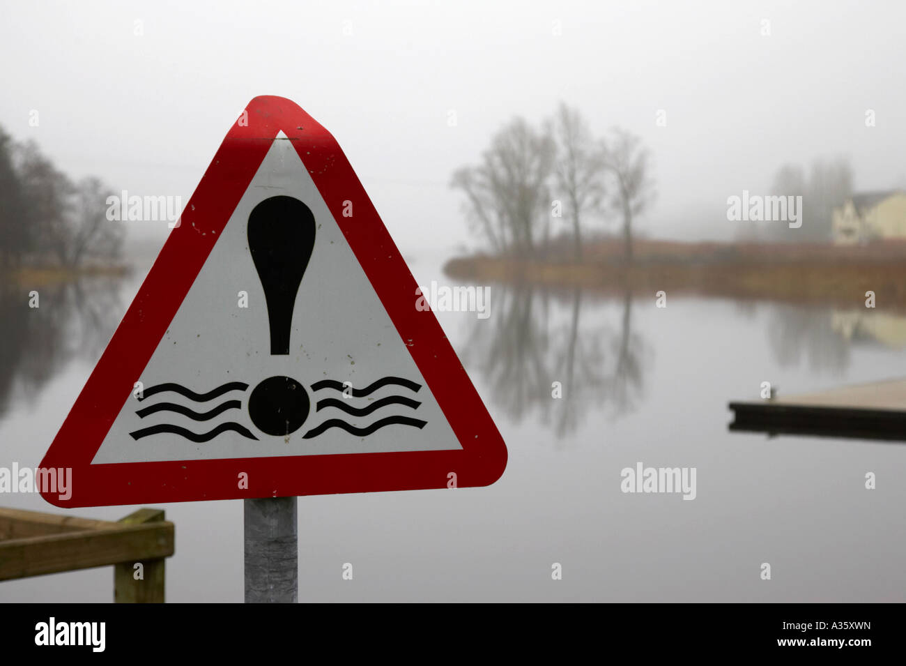 red triangular danger water sign beside jetty on the river erne in enniskillen on a misty winter day - Stock Image