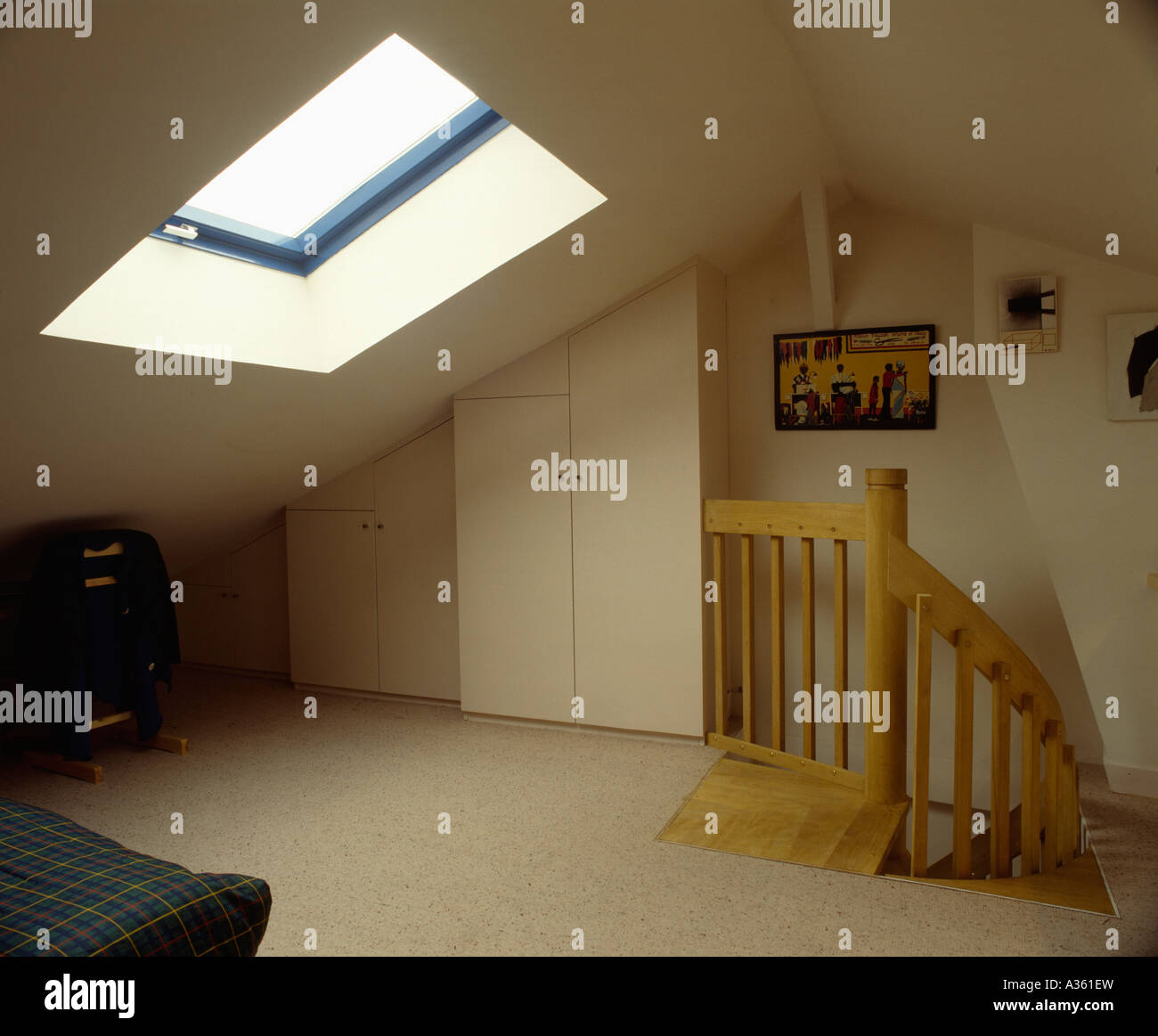 Cream Carpet In Sparsely Furnished Loft Conversion Bedroom With Wooden Banisters On Stairs And Small Skylight In Roof Stock Photo Alamy