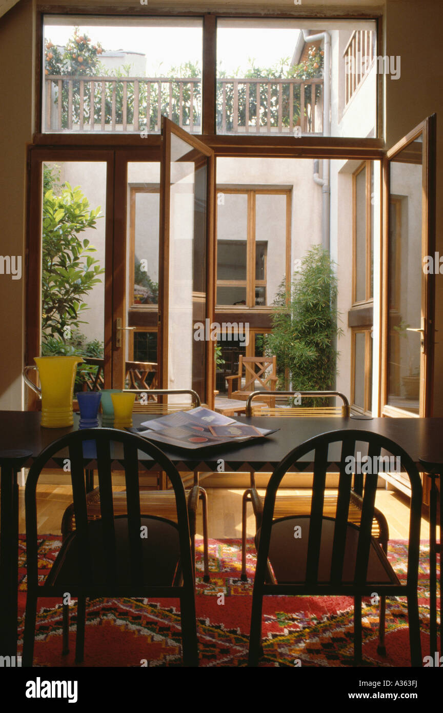 Black Dining Table And Chairs In Modern Room With Open Glass Patio Doors To Small Courtyard