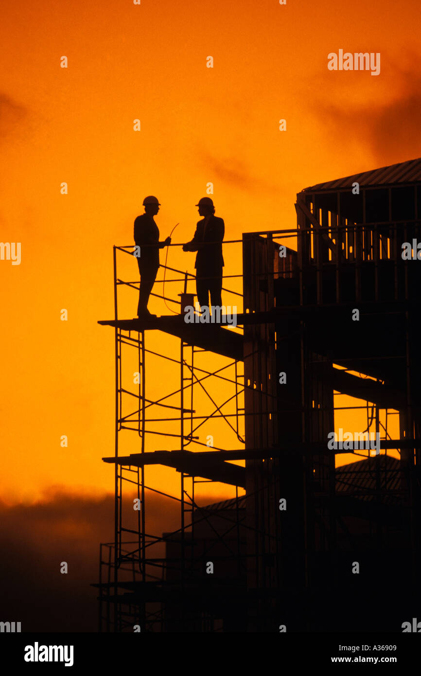silhouette of two construction workers standing on high rise contruction scaffolding - Stock Image