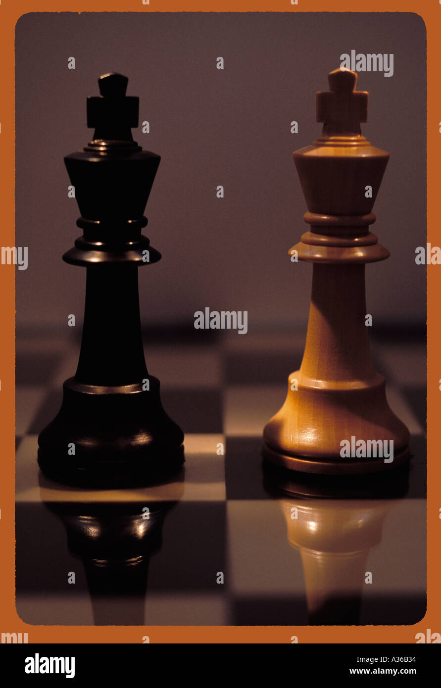 Two kings standing opposite each other on chessboard - Stock Image