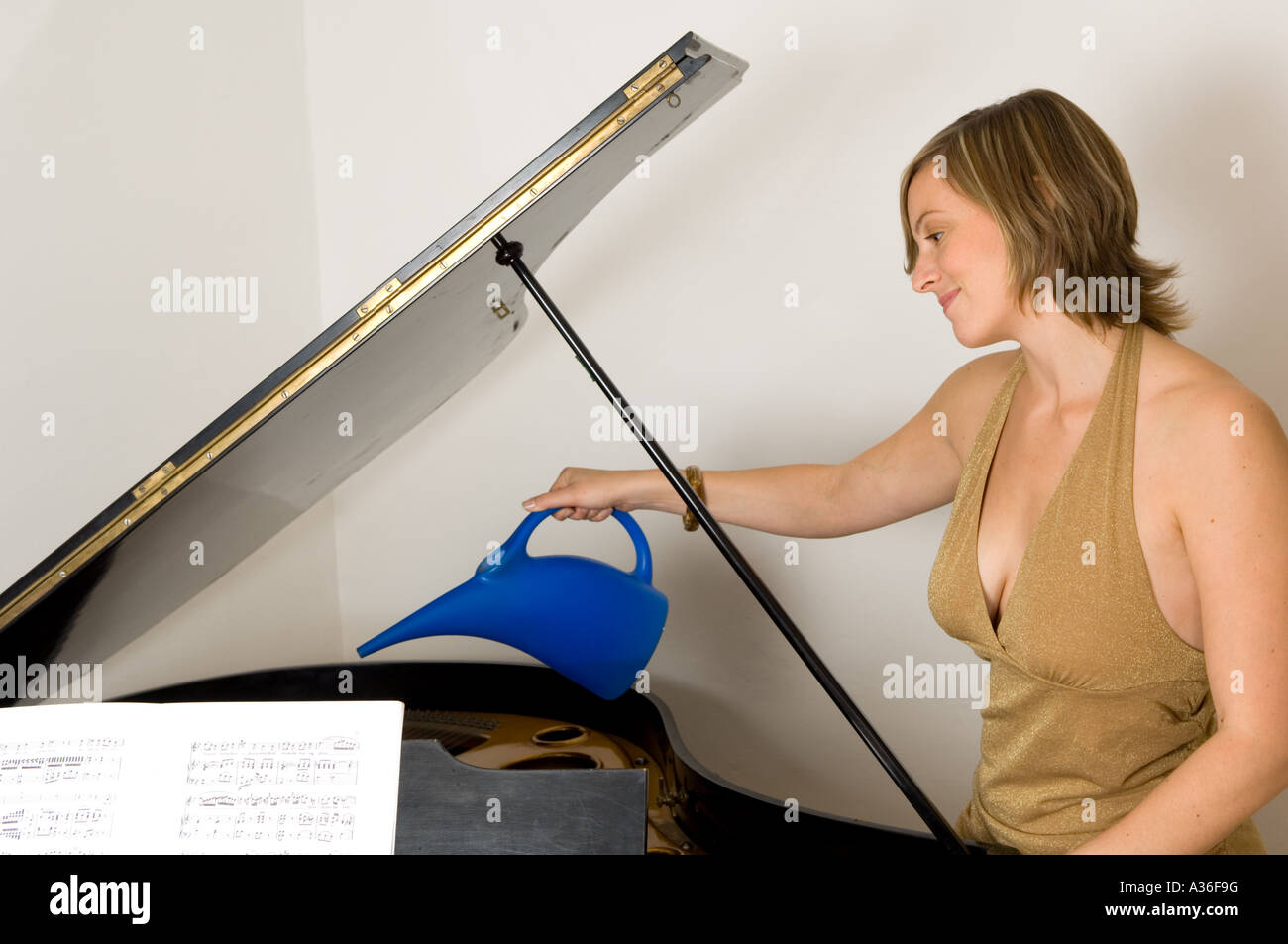 Young woman with grand piano, watering strings - Stock Image